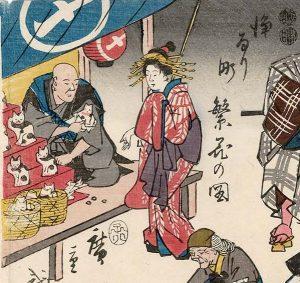 "Drawing of a stall selling Maneki-neko figures in 1852. ""Joruri-machi Hanka no zu"" by Utagawa Hiroshige, 1852. Public Domain."